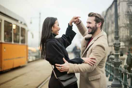a happy couple dancing on sidewalk
